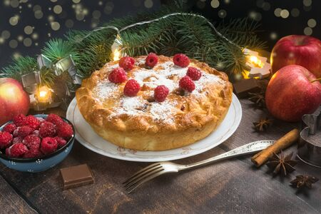 Delicious raspberry pie with berry jam, icing sugar and spices for Thanksgiving or Christmas on dark background.Christmas lights.Apples, chocolate, garlands.Festive dinner.Christmas eve.Party.Close up Foto de archivo - 133816884