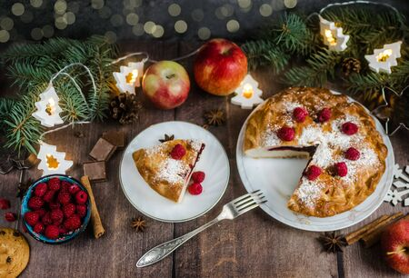 Delicious raspberry pie with berry filling and icing sugar and spices for Thanksgiving or Christmas on a dark background.Next to apples,chocolate and garlands. A party.dinner.Festive dinner.Close up Foto de archivo - 133816883