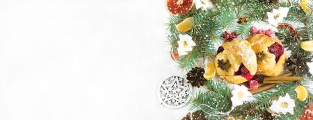 Christmas buns with raspberry jam.Festive pastries with spices, raspberries,jam and tangerines.On a plate on a white background.with branches of Christmas trees in a festive atmosphere.copy space Reklamní fotografie