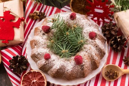 Dairy-free dessert Christmas cake with raisins and raspberries.Natural decorations and gifts from Kraft paper.Zero Waste Christmas. Foto de archivo - 135468639
