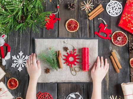 Eco decor.Christmas composition on a rustic wooden background with natural toys, spruce branches,oranges, decorations.Girl makes eco gifts from natural linen,felt.Zero waste.without plastic.top view Foto de archivo - 135468679