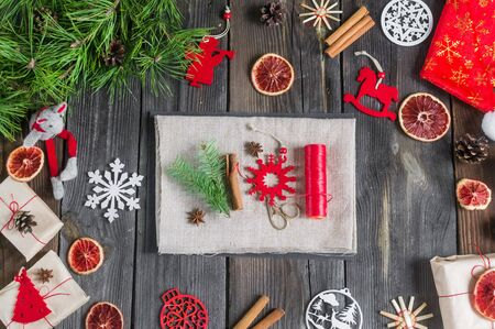 Eco decor.DIY.Christmas composition on a wooden background with natural toys, spruce branches,oranges, decorations.How to create eco gifts from natural linen,felt, thread.Zero waste.top view Foto de archivo - 135468681