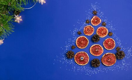 Decorative Christmas tree of oranges and cones on a classic blue background.Concept banner, greeting card, sales.Christmas minimalism.Holiday shopping.Merry Christmas and happy New year. copyspace. Foto de archivo - 135885402