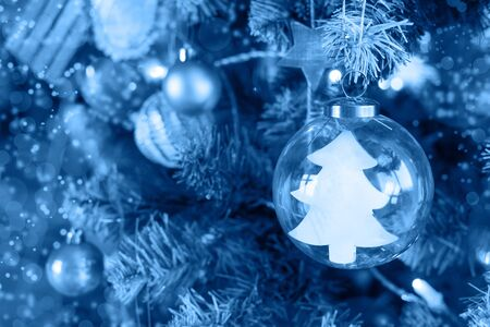 Decorative Christmas tree on a light background with shiny balls and a glass ball inside which is a Christmas tree with copyspace in classic blue. trend color Foto de archivo - 136260853