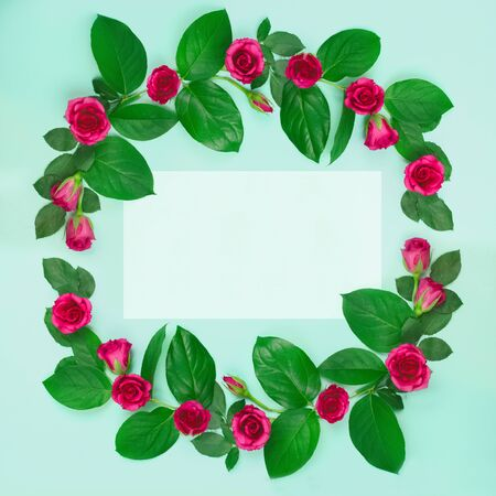 Festive wreath of delicate pink roses with leaves and empty space inside on a blue background.Valentine's day,Wedding,birthday,mother's day.Beautiful greeting card, banner.Flat lay,top view.copy space Foto de archivo - 136512907