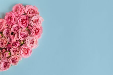Valentine's day greeting card background. Romantic composition with a heart of pink roses on a blue background.Mothers day.Banner for advertising the store, website, posters, Copy spase. Wreath.Frame. Foto de archivo - 137841737