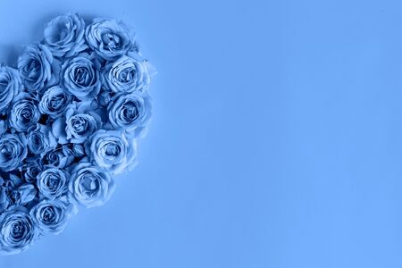 Valentine's day heart made of delicate roses in a classic blue color on a blue background.Holiday card, banner for sale in the store.Spring wreath of flowers-a gift to your loved ones.March 8 Foto de archivo - 137994355