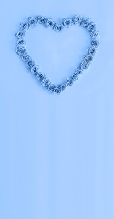 Valentine's day heart made of delicate roses in a classic blue color on a blue background.Holiday card, banner for sale in the store.Spring wreath of flowers-a gift to your loved ones.March 8.vertical Foto de archivo - 138473233