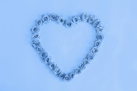 Valentine's day heart made of delicate roses in a classic blue color on a blue background.Holiday card, banner for sale in the store.Spring wreath of flowers-a gift to your loved ones.March 8 Foto de archivo - 138473264