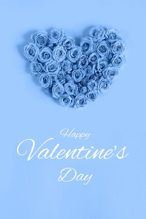 Valentine's day heart made of delicate roses in a classic blue color on a blue background.Holiday card, banner for sale in the store.Spring wreath of flowers-a gift to your loved ones.March 8.vertical Foto de archivo - 138473286