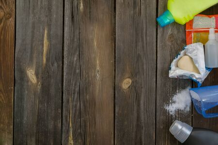 Dirty children's clothes are scattered on a wooden table next to washing powders and soap.Concept washing dirty spots, the best means of cleaning kids clothes.copy space.Mock up.Flat lay