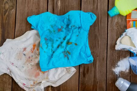 Dirty children's clothes are scattered on a wooden table next to washing powders and soap.Concept washing dirty spots, the best means of cleaning kids clothes