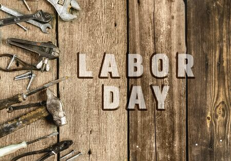 Labor Day. Congratulatory text on an old rustic wooden background surrounded by various tools in the workshop.A greeting card or banner for your store or website.FLat lay.Top view.