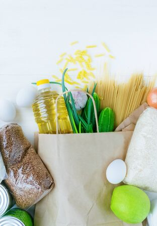 Delivery food.Paper bag with fresh food,macaroni,canned food,greens,vegetables,oil.