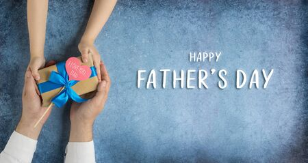 Happy fathers day.Gift in the hands of daughter and father on a blue background.Banner for the sale in store,website.Greeting card Banque d'images