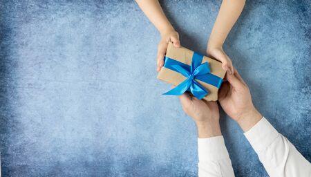 快乐的父亲节。礼物在女儿和父亲的手中在一个蓝色的背景。我爱你,爸爸。家庭的爱和健康。横幅销售在商店,网站。贺卡。副本的空间。俯视图
