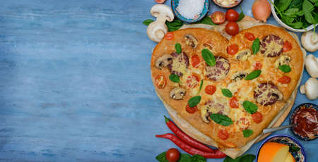 Homemade Delicious pizza heart for Valentine's Day made of yeast-free dough with vegetables, tomatoes, herbs, cheese, prepared at home for festive dinner. Instructions. DIY.copy space.banner