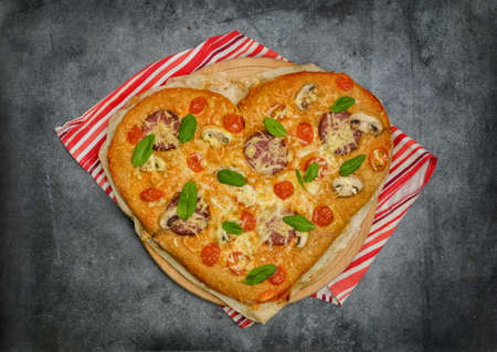 Homemade Delicious pizza heart for Valentine's Day made of yeast-free dough with vegetables, tomatoes, herbs, cheese, prepared home for festive dinner.Instructions.DIY.Banner.Flat lay.Top view