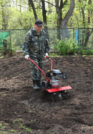 cultivator: A man working in the garden preparing ground cultivator at the beginning of the spring season