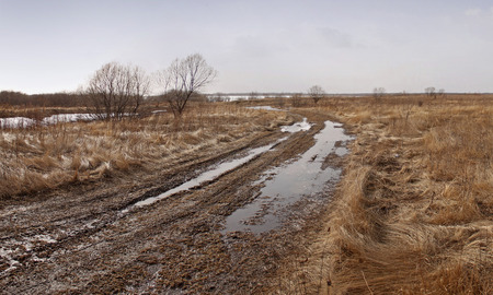 land slide: Spring road in puddles and mud with a gray sky