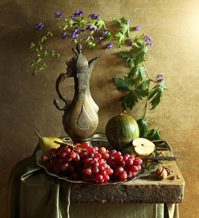 Still life with grape, apple and old jug on a stone table Banco de Imagens