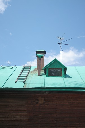 building feature: The roof of a village house green against the blue sky with clouds