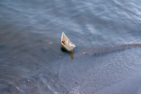 Paper boat floating on the river