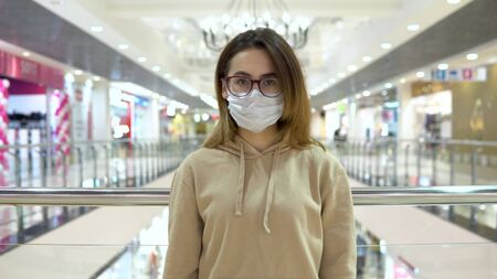 Young woman in medical mask at the mall. The masked woman protects herself from the epidemic of the  virus. The camera approaches a woman 2019-nKoV