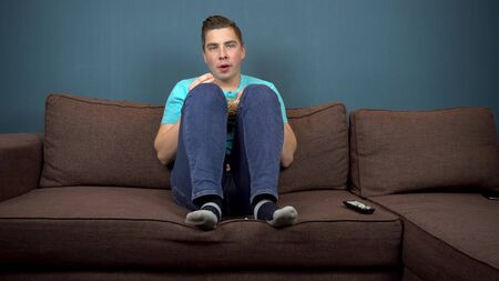 A young man is watching TV and eating popcorn. The guy is watching TV carefully. The man climbed his feet on the sofa. The view from the TV. Looking at the camera