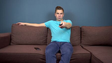 A young man sits on a sofa and watches TV. The view from the TV. Looking at the camera