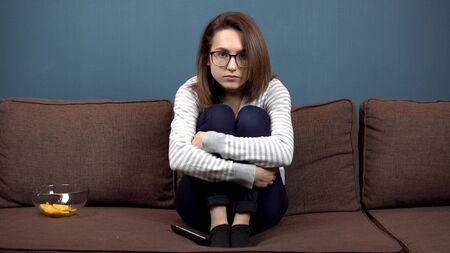 A young woman in glasses reads nervously watching television. The girl climbed onto the sofa and hugged her legs. Nervous when watching TV Imagens