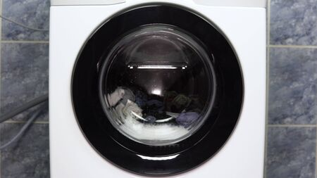 The washing machine is working. A washing machine spins a drum filled with clothes. Stockfoto