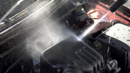 Washes away dirt from a car engine with a high-pressure water jet close-up. Special detergent for car wash. Washes a car in front of the house.