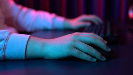 A young man types on a computer keyboard and works with a mouse. Hands close up. Blue and red light falls on the hands.