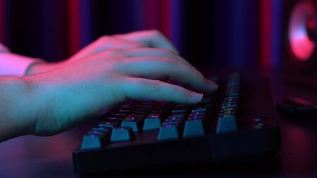 A young man is typing on a computer keyboard. Hands close up. Blue and red light falls on the hands.