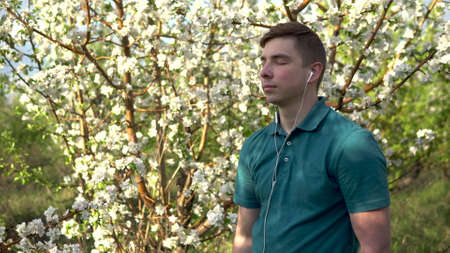 Young man in nature with headphones in his ears. A man listens to music while standing against a flowering tree.