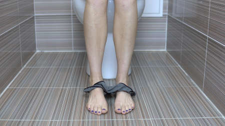 Woman shot gray tanga panties sitting on the toilet. Girl with shaved legs on the toilet