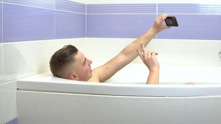 A young man lies in the bath and takes a selfie on the phone. A man relaxes in the bath.