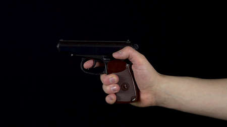 A man makes a shot from a pistol. Pistol in hand close-up makes a shot. On a black background