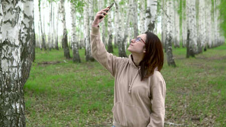 A young woman is looking for a cellular network in a birch forest. A girl is talking on the phone, but the connection is interrupted. The woman is nervous.