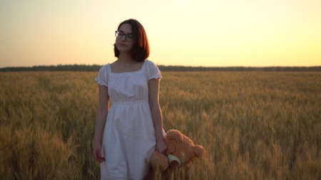 A young woman walks through a wheat field with a teddy bear at sunset. Girl holds a teddy bear in hand front view.