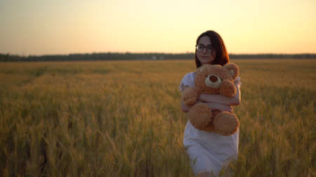 A young woman walks through a wheat field with a teddy bear at sunset. Girl hugs a teddy bear in hands front view.