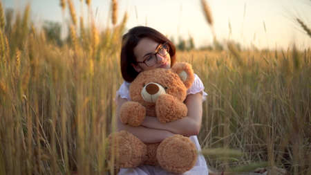 A young woman sits in a dried wheat field with a teddy bear. Girl hugs a teddy bear in hands front view.