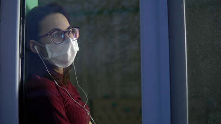 A young woman is sitting at home in quarantine with headphones in her ears. A girl sits on a window sill in a mask and listens to music and then looks out the window. View behind the glass.