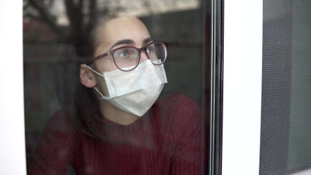A sad young woman is sitting at home in quarantine. A girl looks out the window and puts her hand to the glass. View behind the glass. Imagens