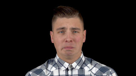 The young man is crying. Emotional man crying on a black background closeup