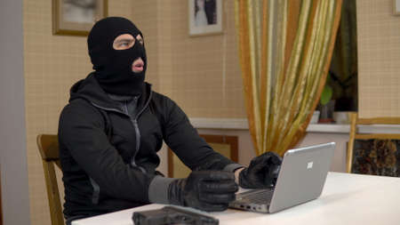 A robber is trying to hack into a laptop. A masked thug is sitting in a house and cannot hack into a laptop. Theft of data from a computer. 스톡 콘텐츠