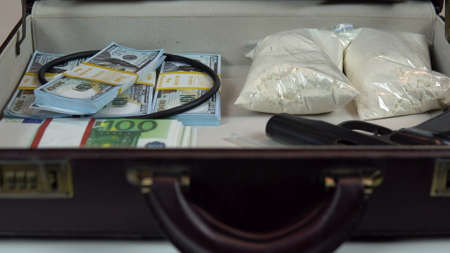 A man opens a case closeup. In an open case are dollars and drugs