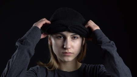 A young woman is putting on a balaclava mask. Bandit on a black background close-up.