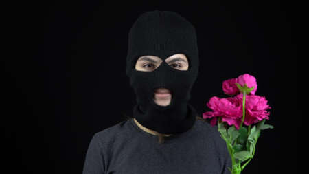 A Woman in a balaclava mask is standing with flowers. Bandit sniffs a bouquet of pink flowers on a black background.